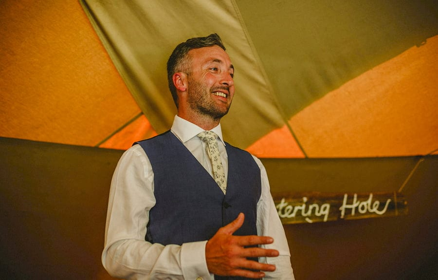 The groom shares a joke with everyone in the tipi