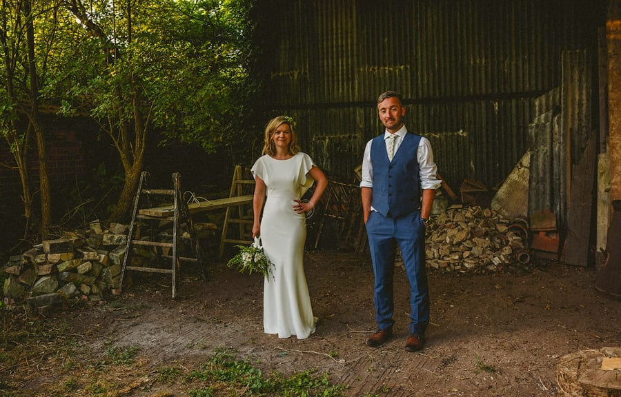 Claire and Dan stand in front of the open barn and pose for a photograph
