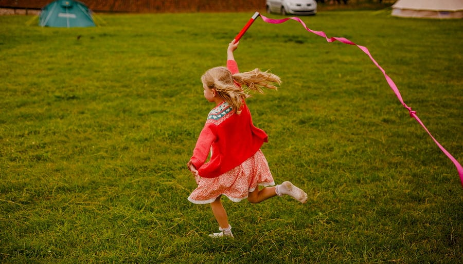 A girl runs through a field at Fernhill Farm carrying a long red ribbon through the air