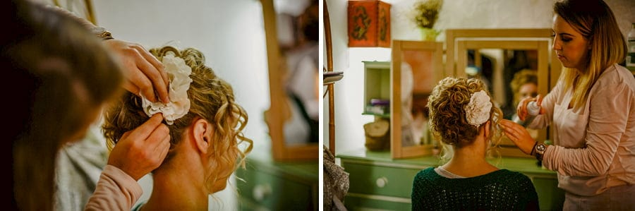 The makeup artist places a hair clip into the hair of the bride