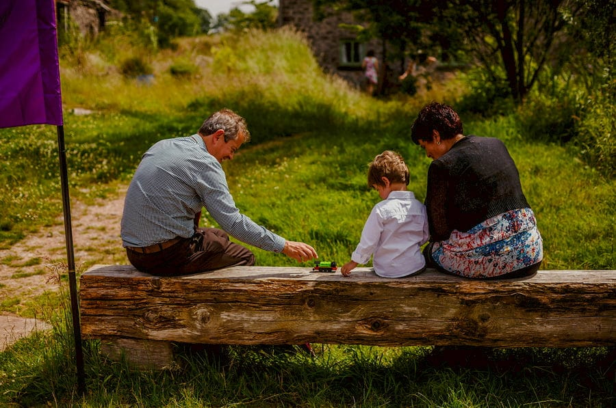 A little boy sits on an old tree stump with his grandparents