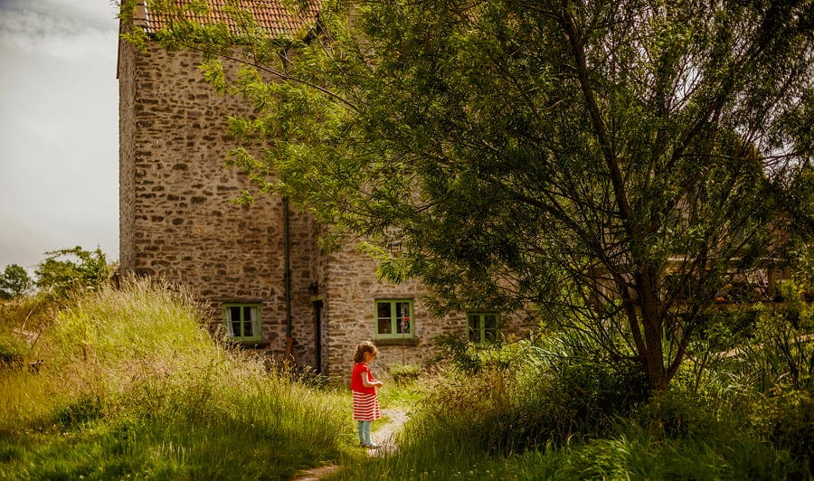 A little girl waits on her own outside the cottage at Fernhill Farm in Somerset