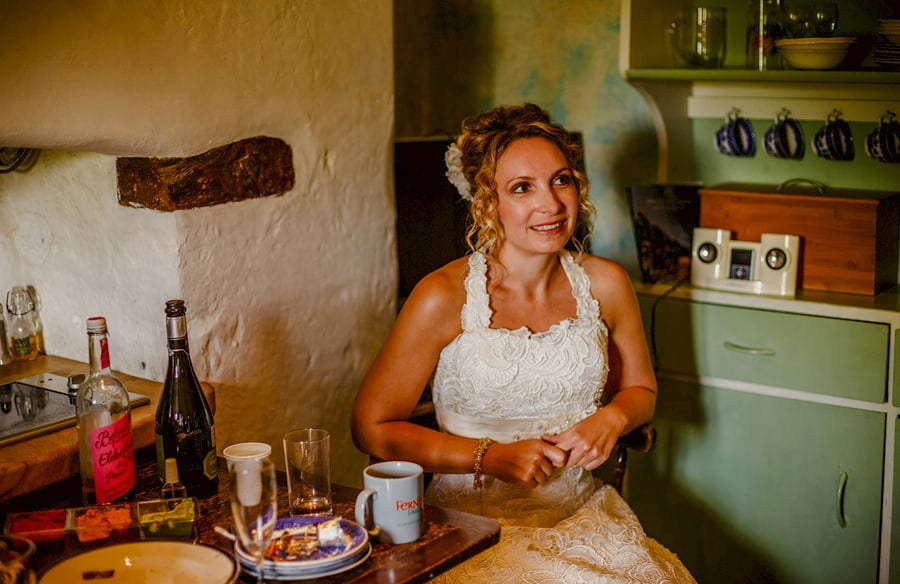 The bride sits at a wooden table in the kitchen of the cottage