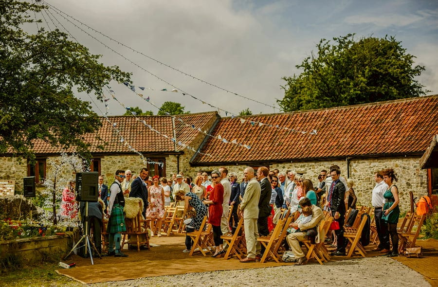 The guests stand and wait for the bride and her father in the courtyard at Fernhill Farm
