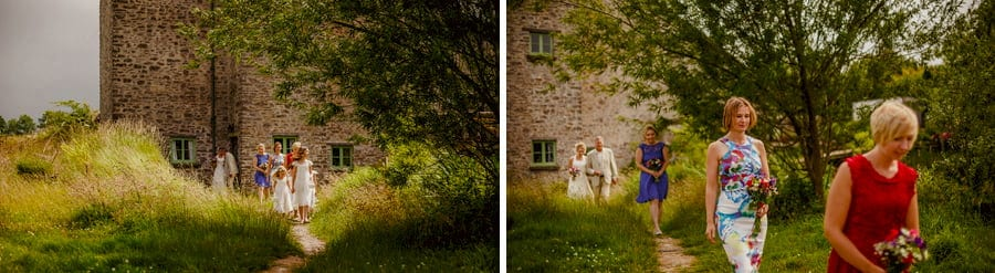 Bridesmaids walk away from the cottage towards the outdoor wedding ceremony at Fernhill Farm