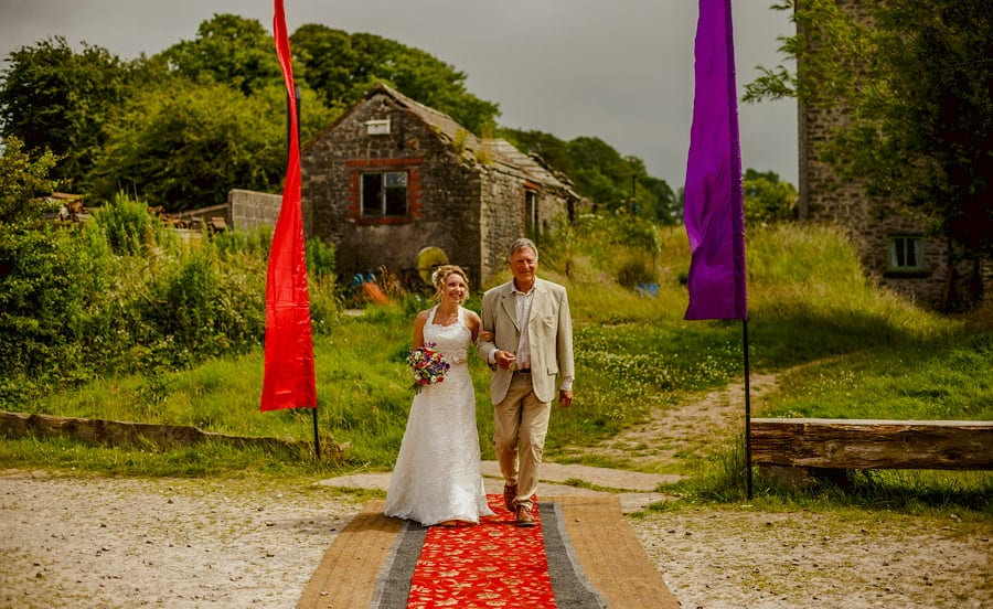 The bride and her Father walk towards the outdoor wedding ceremony at Fernhill Farm in Somerset