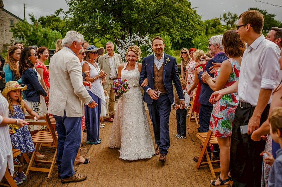 The bride and groom walk down the aisle of the outdoor wedding ceremony at Fernhill Farm