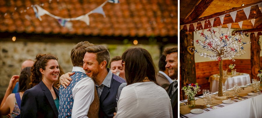 A wedding guest puts his arm around the groom in the courtyard at Fernhill Farm