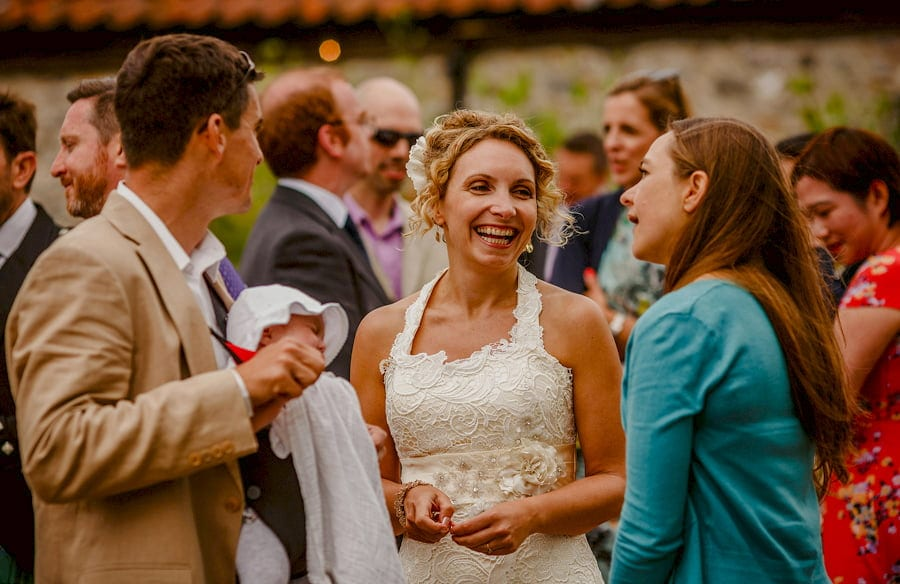 The bride laughs with friends in the courtyard at Fernhill Farm