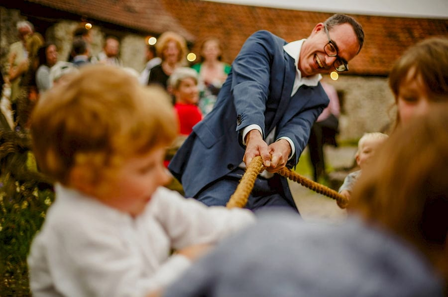 A wedding guest pulls a rope with children in the courtyard at Fernhill Farm
