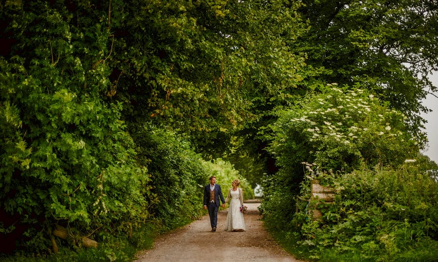 The bride and groom walk along a path at Fernhill Farm