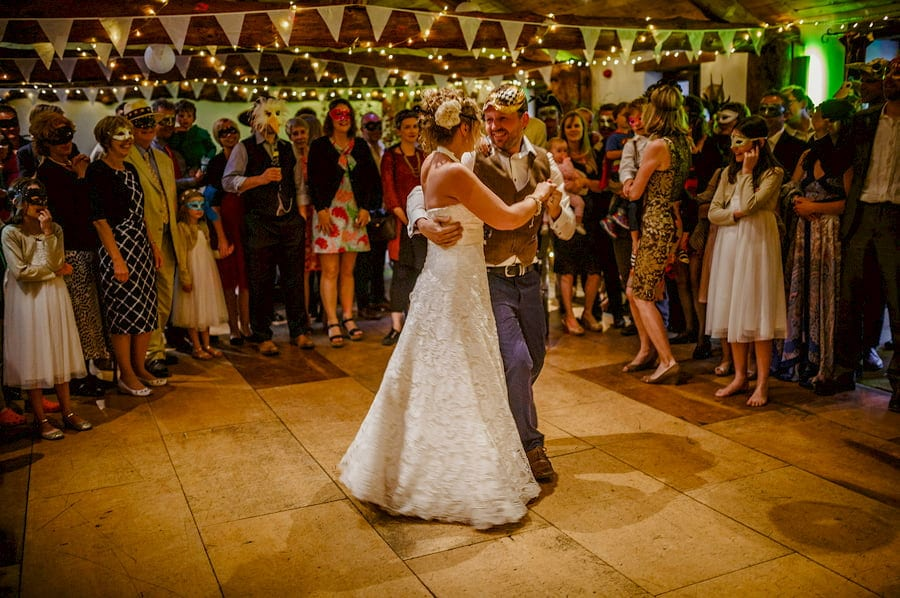 The bride and groom hold each other and dance on the dancefloor in the barn at Fernhill Farm