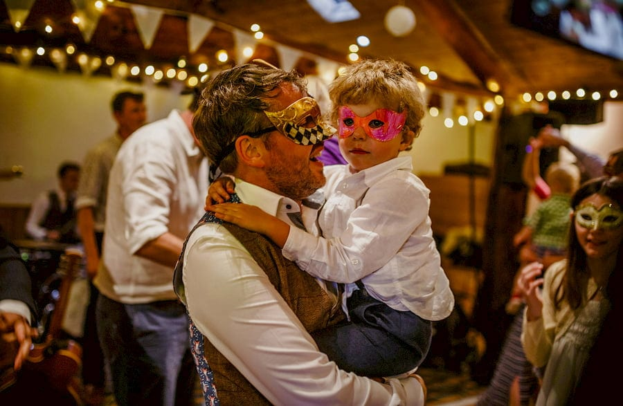 The groom holds his son in his arms on the dancefloor in the barn at Fernhill Farm