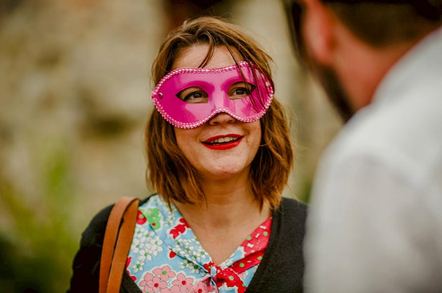 A wedding guest wears a pink mask and chats to a friend in the courtyard