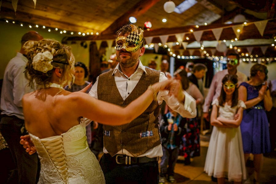 The bride and groom wear masks and dance in the barn at Fernhill Farm