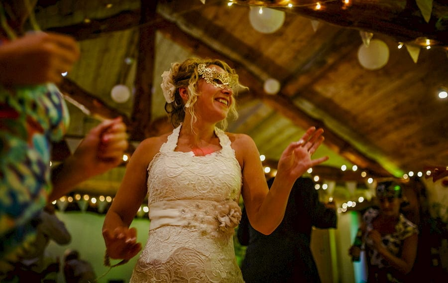 The bride dancing and wearing a gold mask smiles to a friend on the dancefloor