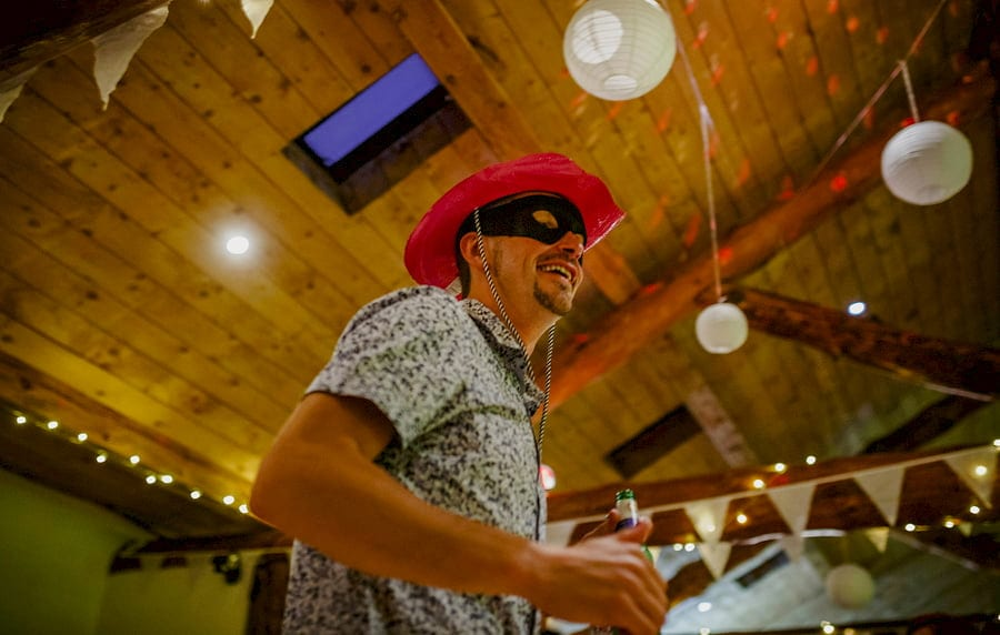 A wedding guest wearing a red hat and black face mask dancing in the barn at Fernhill Farm