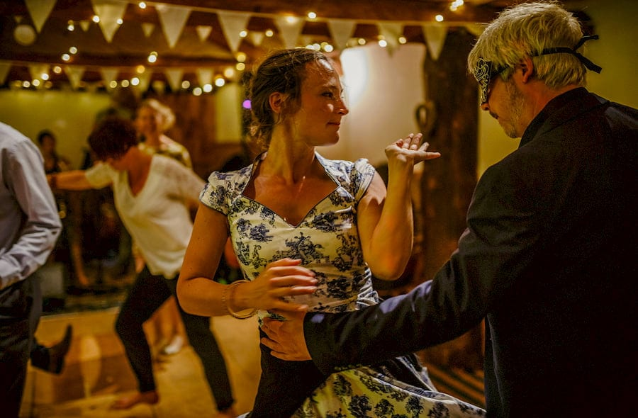 A lady dances with a man on the dancefloor in the barn at Fernhill Farm