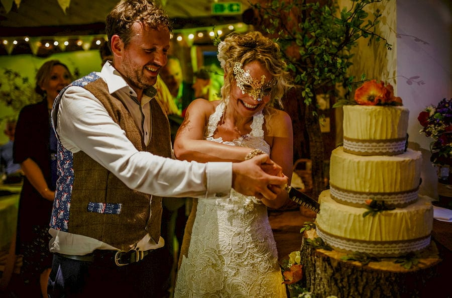 The bride and groom stand next to each other and cut the cake in the barn