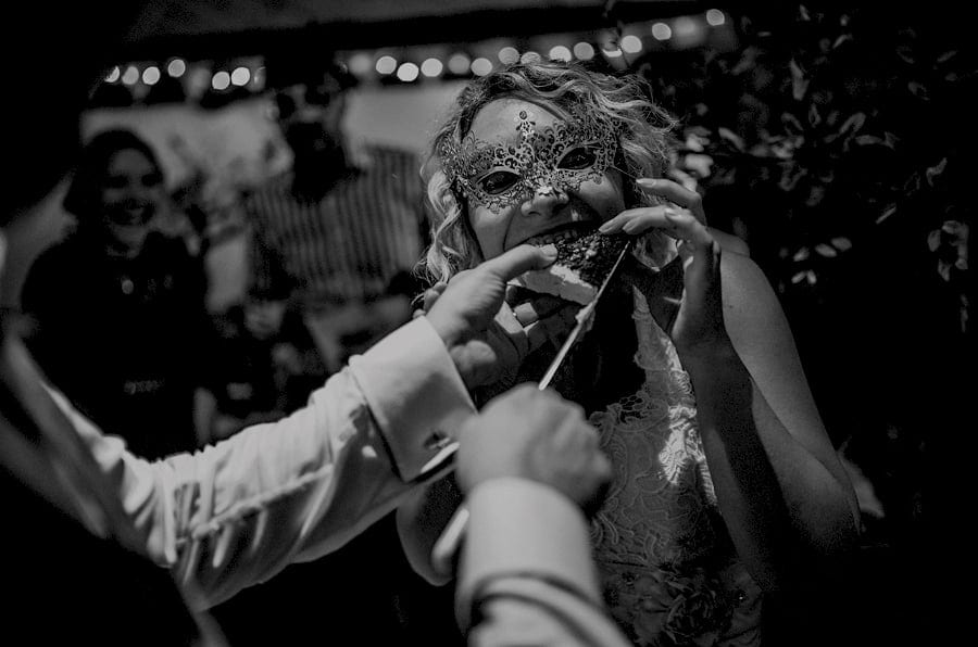 The groom places a piece of cake into the mouth of the bride