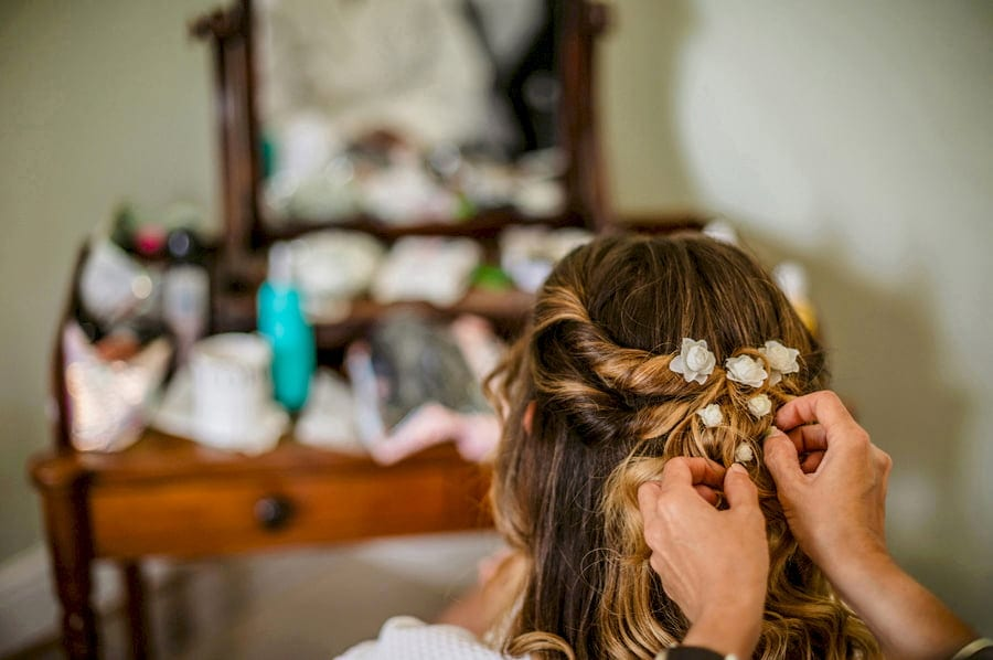 The brides flowers are placed into her hair