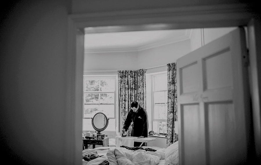 The groom irons his shirt at Pennard house, Somerset