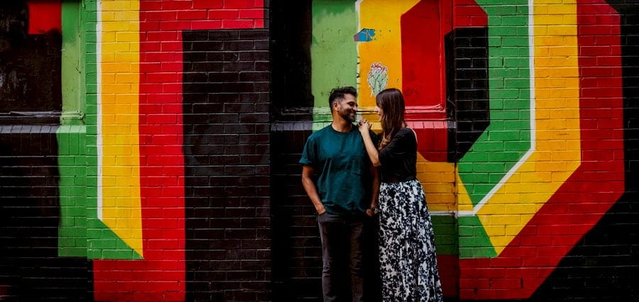 A man and lady stand against a multi coloured painted wall and look at each other