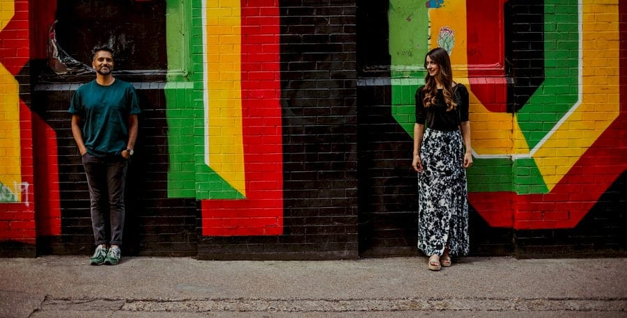 A man and lady stand apart from each other and pose for a photograph against a multi coloured painted wall