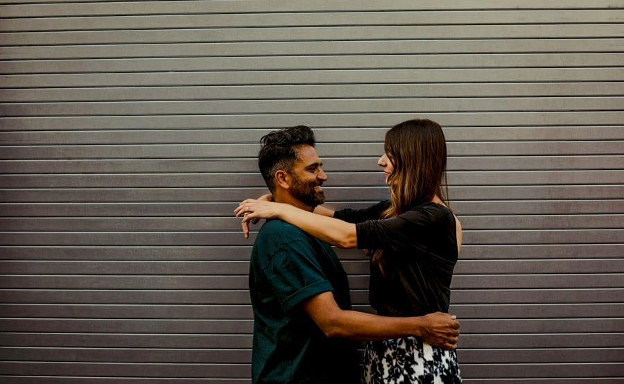 A man holds the lady around the waist and the lady places her arms across the man's shoulders as they look at each other against a large metal shutter