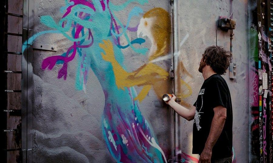 A man spray paints a wall