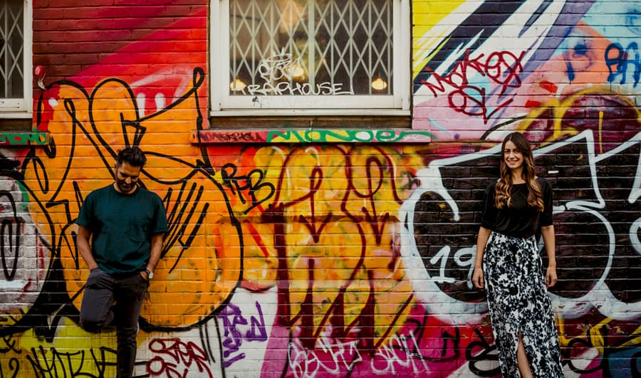 The man looks down on the floor and the lady looks at the camera as they pose for a photograph against a large brick multi coloured wall