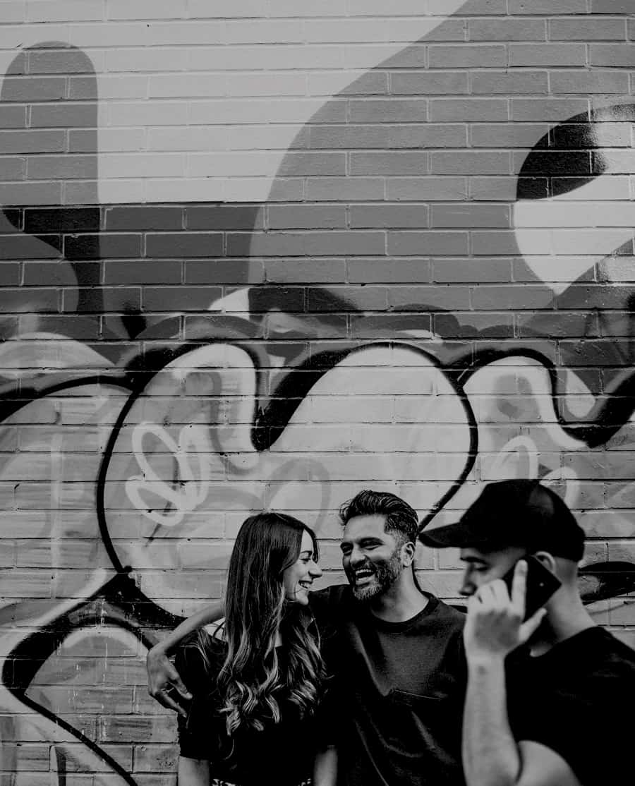 A man and lady share a joke with each other and laugh against a wall as a man with a mobile phone and a black cap walks passed