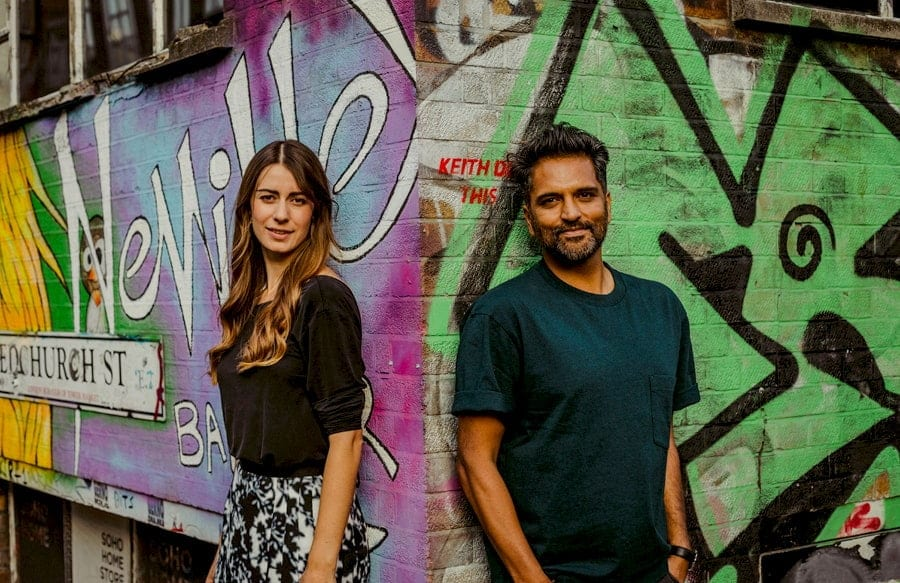 A lady and a man pose for a photograph against a wall in Shoreditch, London