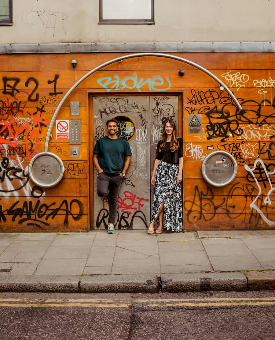 A lady and a man lean against a doorway and pose for a photograph in Shoreditch, London