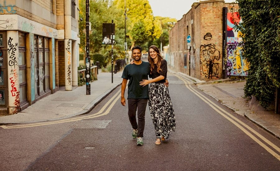 A lady and a man walk side by side and smile as they pose for a photograph in the middle of a road in Shoreditch in London