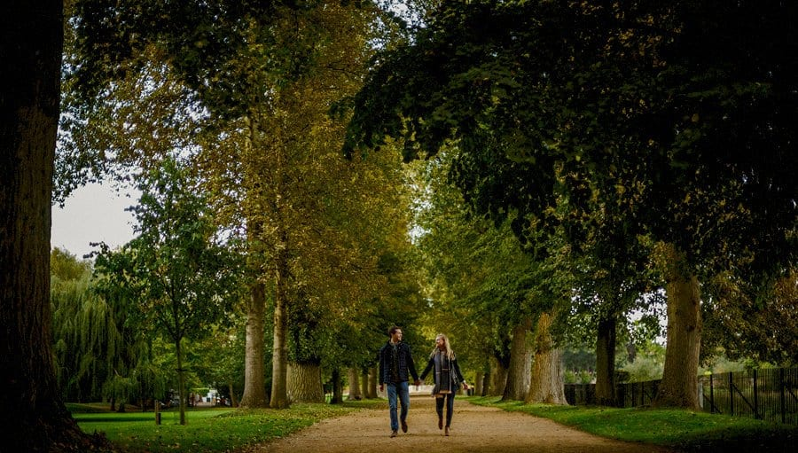 A lady and a man hold each others hand and look at each other as they walk through a park in Oxford