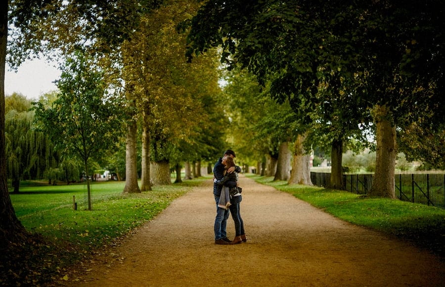 A lady and a man embrace each other as they stand in the middle of a path in a park in Oxford