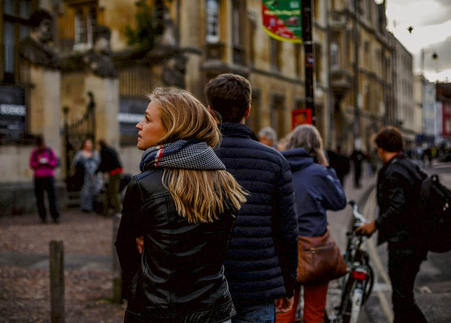 A lady walks behind a man in the city centre of Oxford
