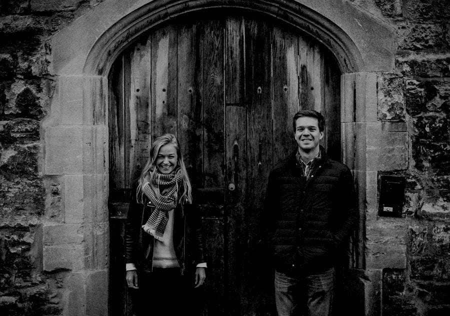 A lady and a man stand next to each other against an old large wooden arched door in Oxford