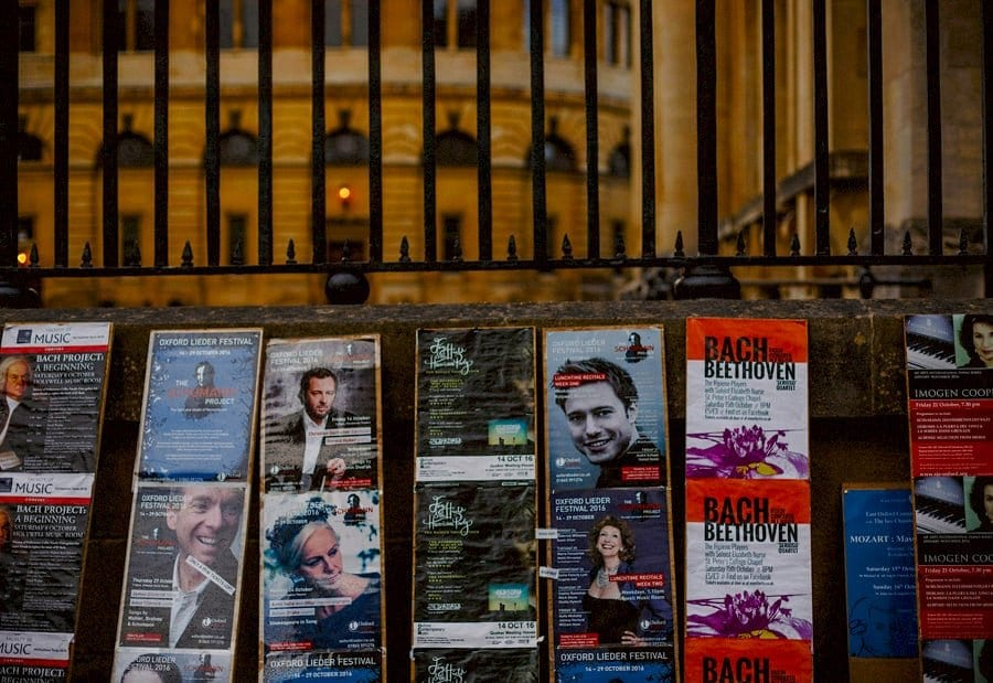 Small posters advertising opera performances being performed in Oxford are being displayed against a wall
