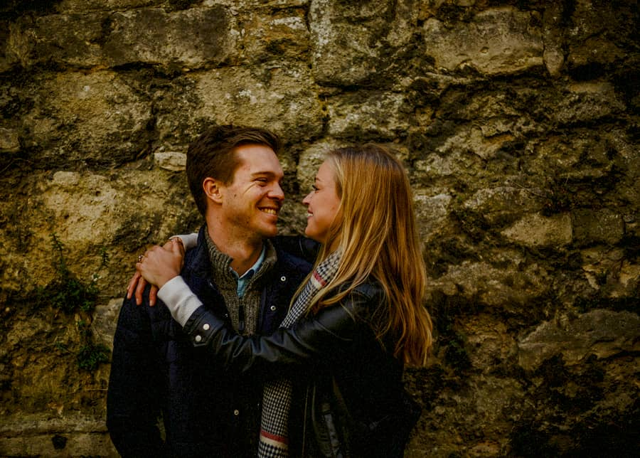 A lady places her arms around the shoulders of a man and they smile at each other against an old brick wall in Oxford