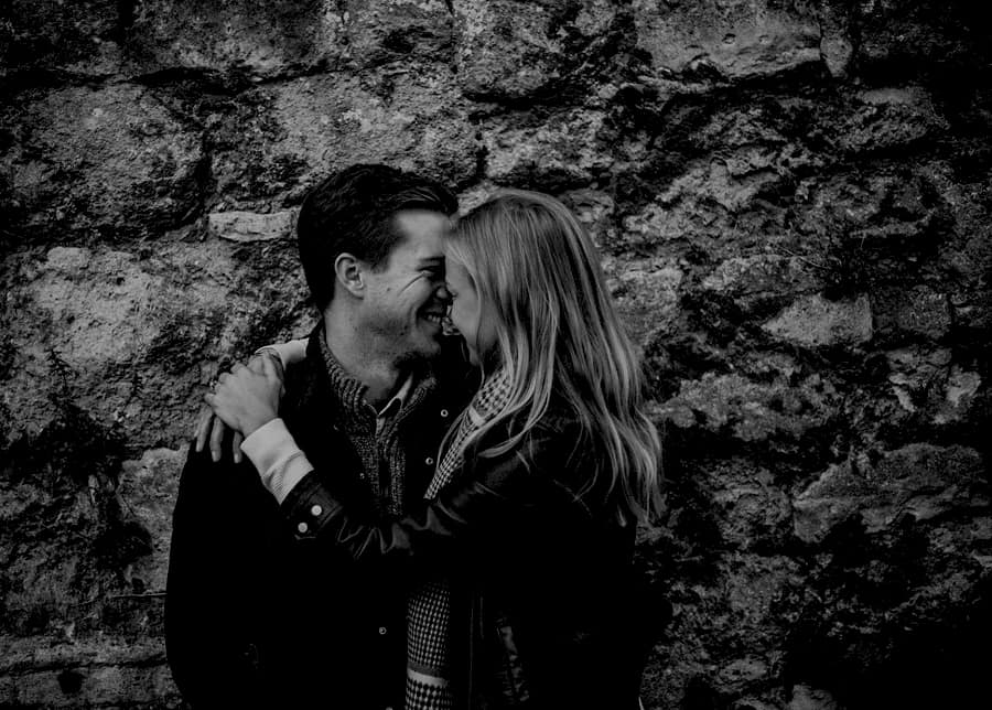 A lady and a man place their heads next to one another and laugh and they embrace each other against an old brick wall