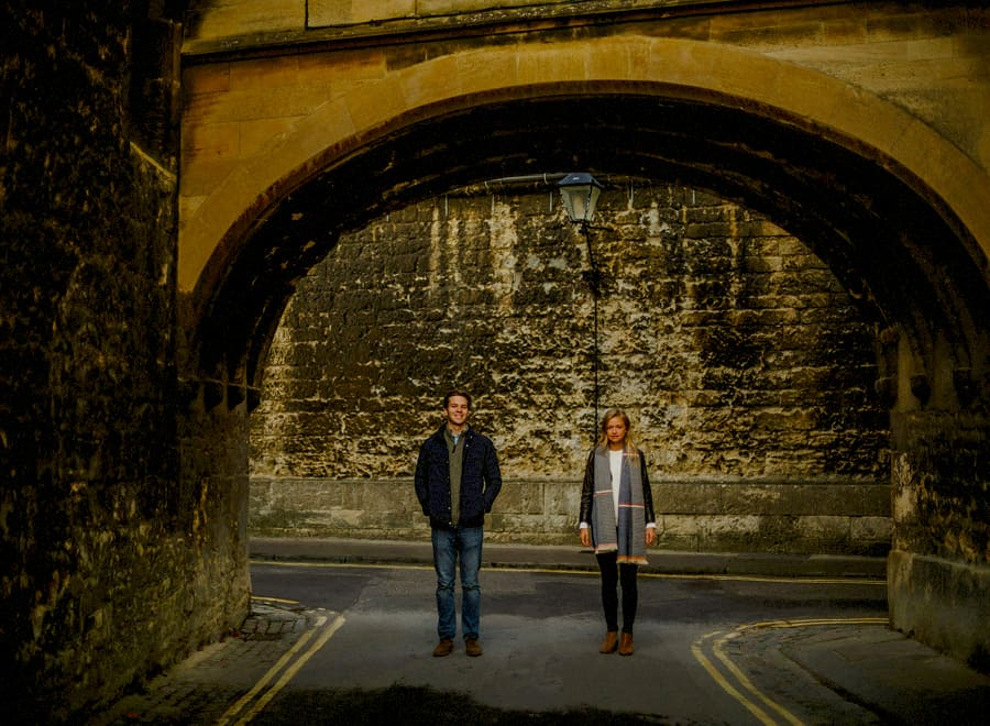 A man and lady stand in the middle of a road apart from each other and pose for a photograph in Oxford town centre