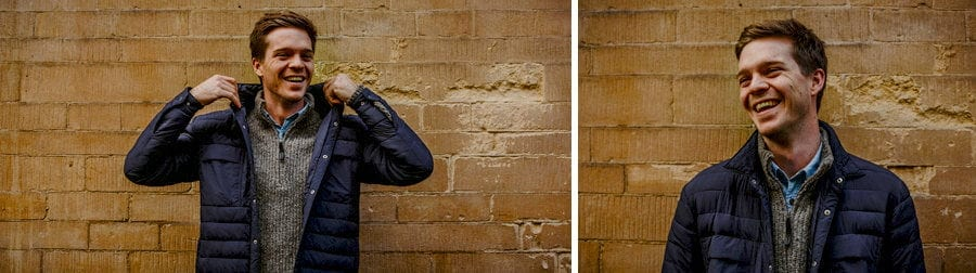 A man lifts the collar of his coat up and laughs against a wall in Oxford town centre