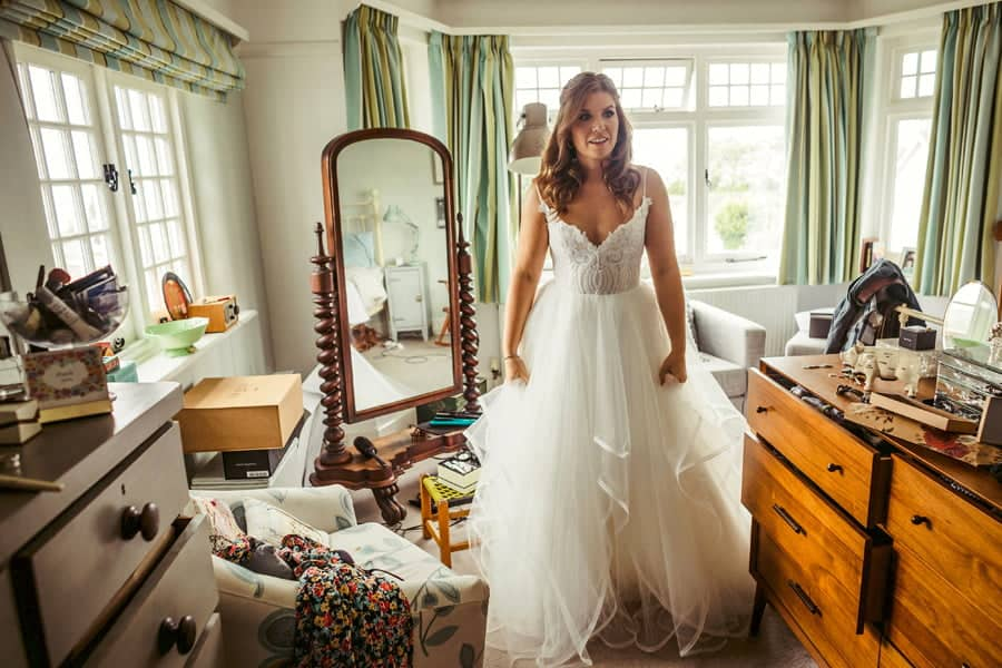 The bride stands in her parents bedroom with her wedding dress on