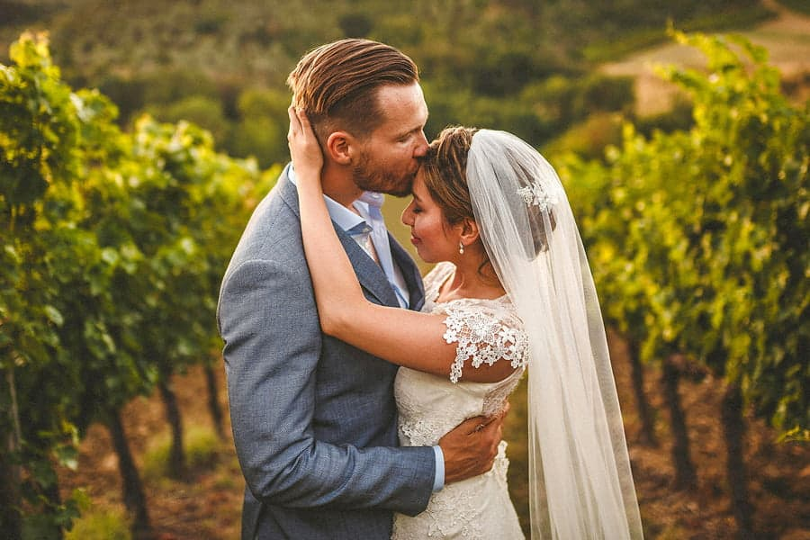 The groom holds the bride and kisses her on the forehead in a field as she puts both her hands on the back of his head