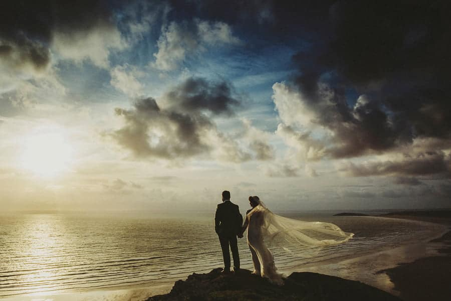 The bride and groom hold each others hand and stand next to each other on the edge of a cliff and watch the sun go down over the sea