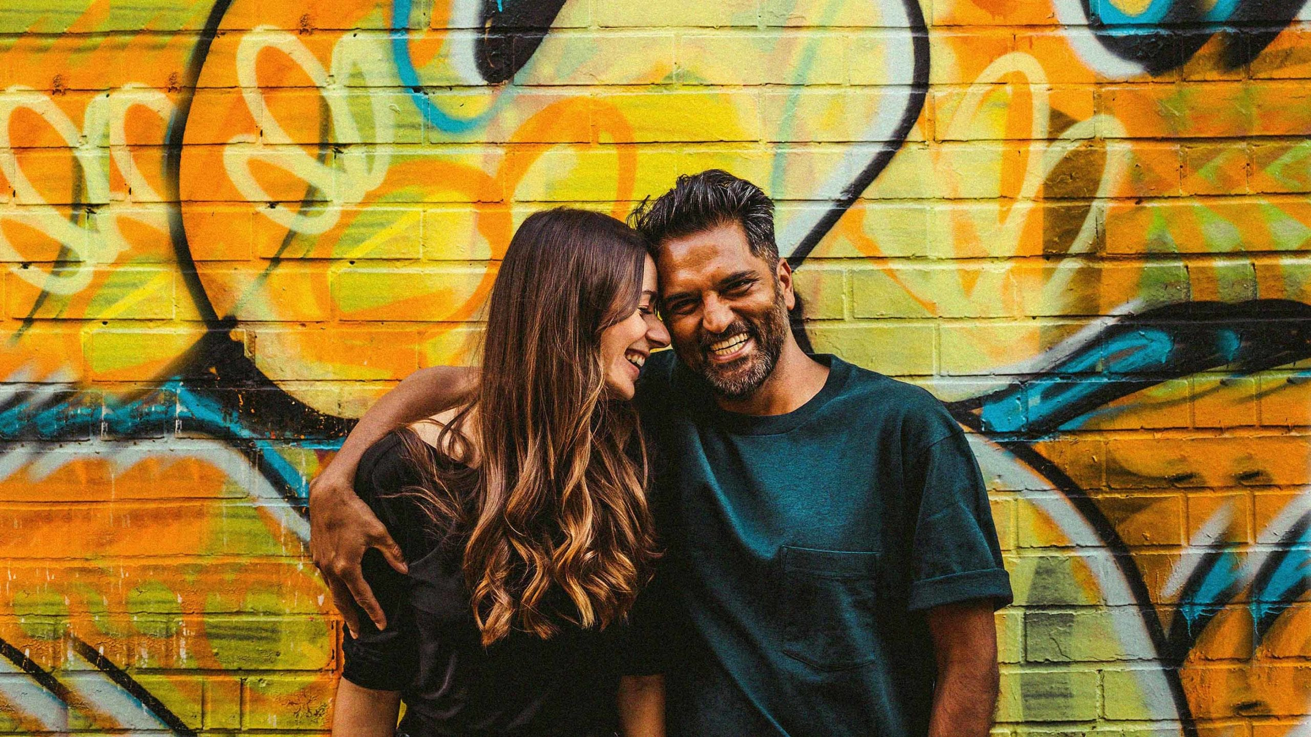 A man and lady stand in front of a multi coloured wall and pose for a photograph as the lady places her forehead onto the side of the man's head