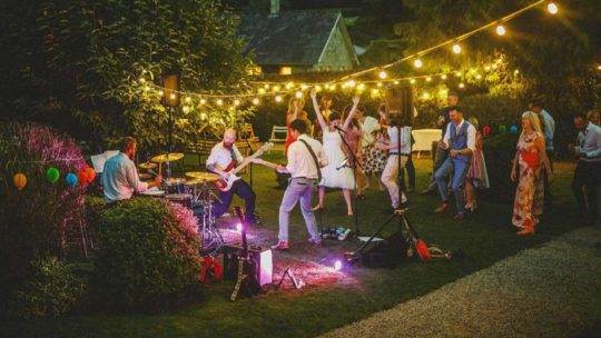 The wedding party dance on the lawn in front of the wedding band