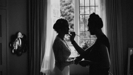 A makeup artist applies lipstick to the lips of the bride as she stands next to a large window in her room